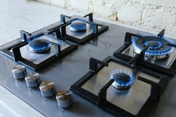 A lit gas cooktop in a residentail property